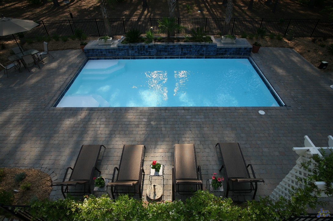 rectangular pool located in backyard with brick pavers