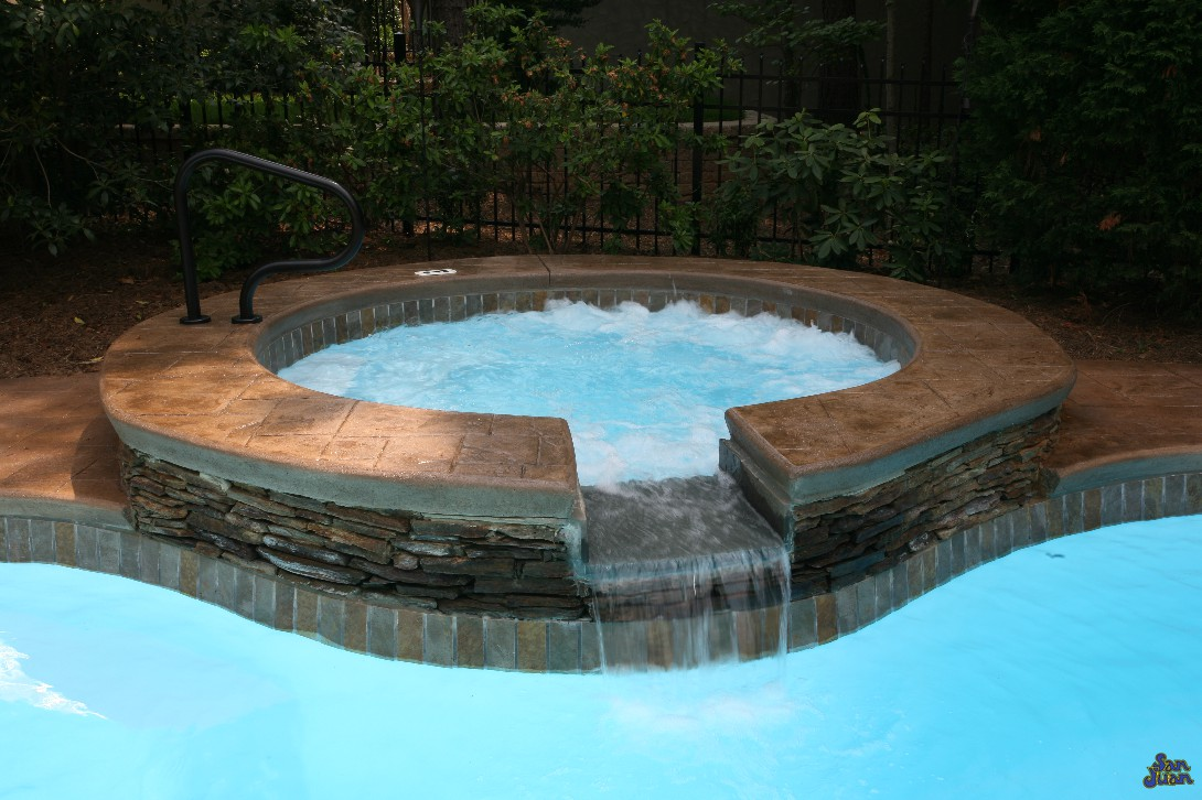 Catalina Fiberglass Pool with stamped and stained concrete on raised wall with water fall