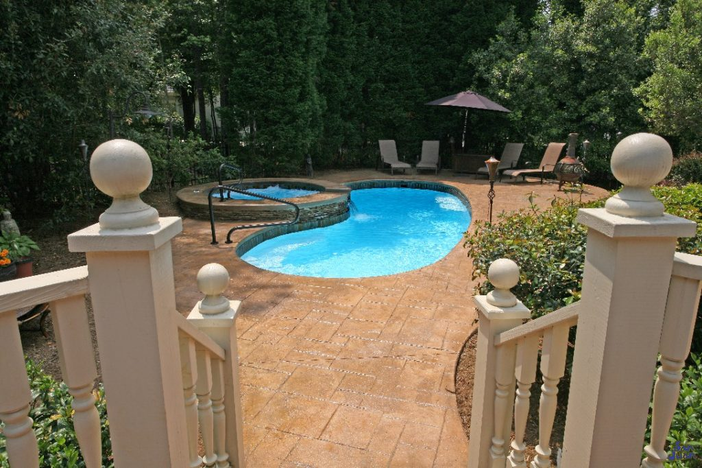 Catalina Fiberglass Pool with travertine pavers and raised spa waterfall