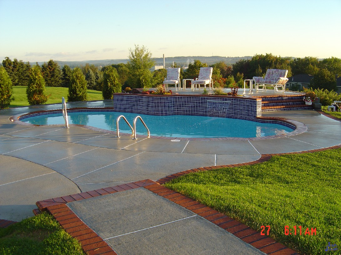 atlantic pool shape with beautiful concrete decking and raised patio