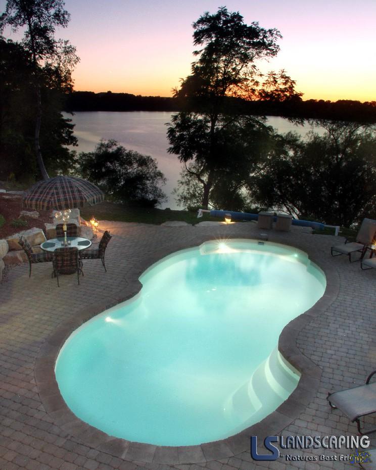 atlantic pool shape with brick pavers outdoor patio next to lake