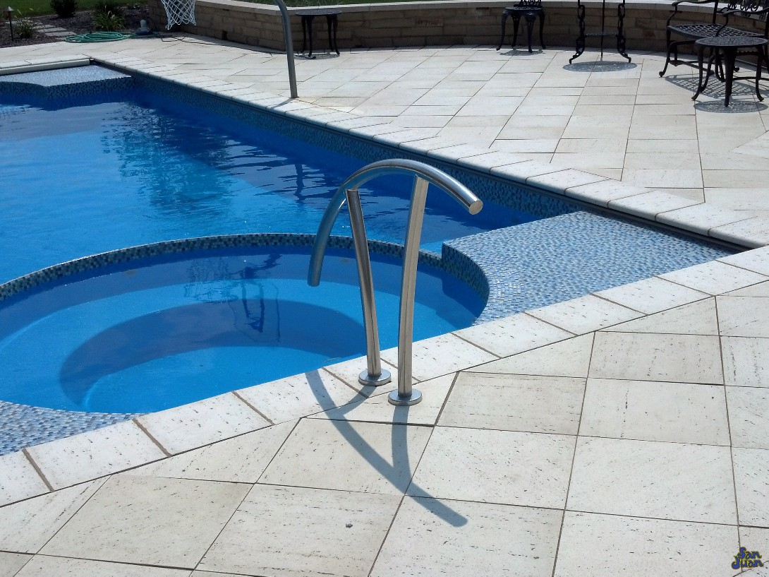 ceasars palace fiberglass pool shape with natural travertine decking and handrail with tile finish