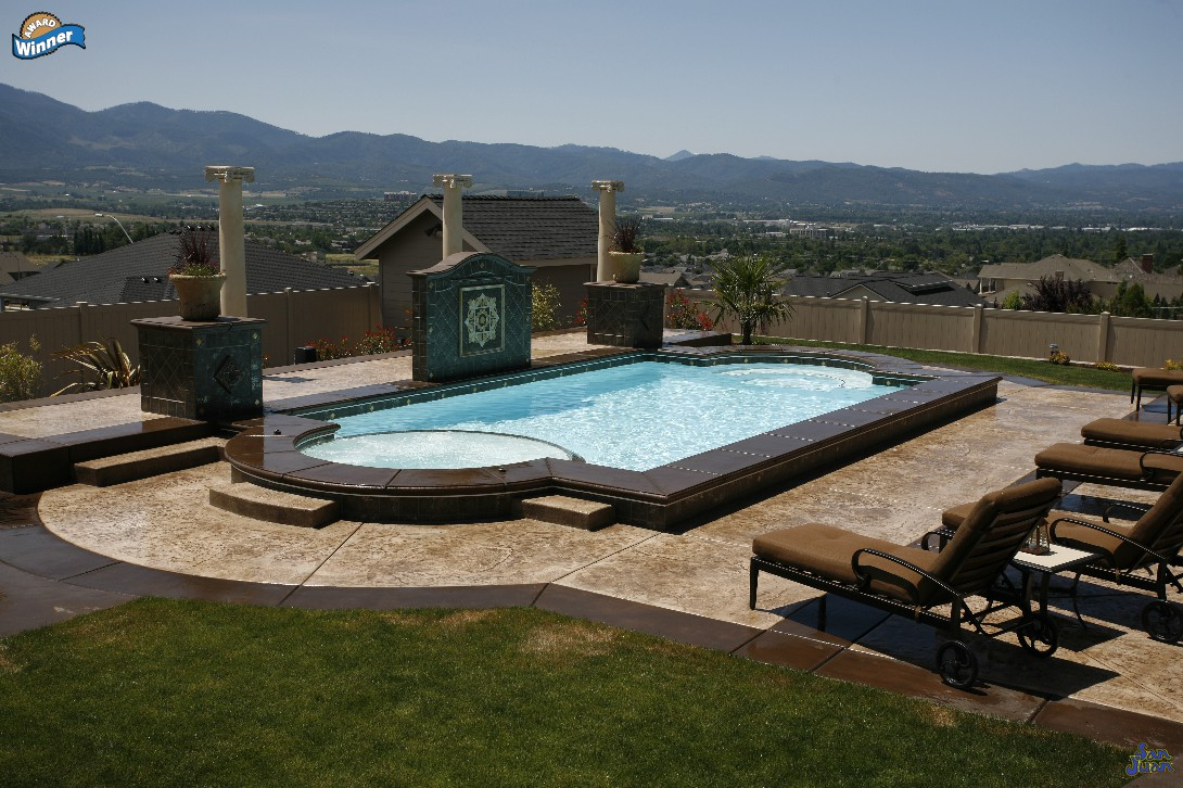 This image shows the caesars palace pool model slightly elevated above the pool deck. There is a raised section of coping bordering this pool that is set on a hill top for a gorgeous view of the surrounding landscape.