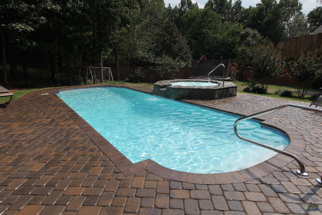 This dolphin pool is complimented by a nice brick paver deck, shallow end handrail & raised spa. For those who may not know, we also sell fiberglass spas and will have much more articles to follow on those in the future!