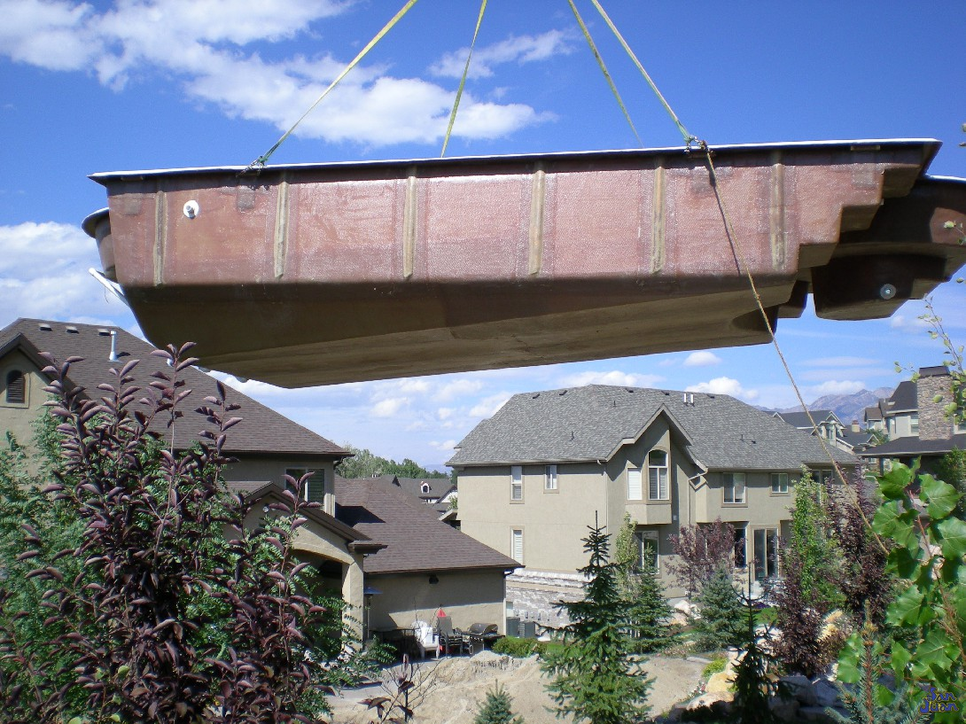 fiberglass pool being lifted over houses during installation