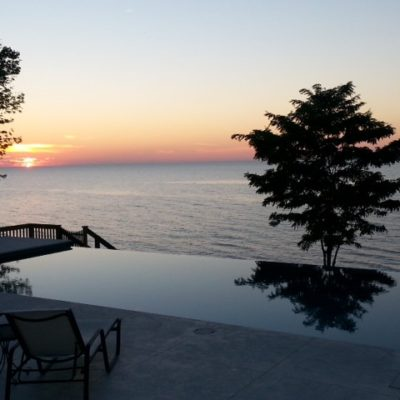 monte carlo fiberglass pool with negative edge located by lake side at sunset