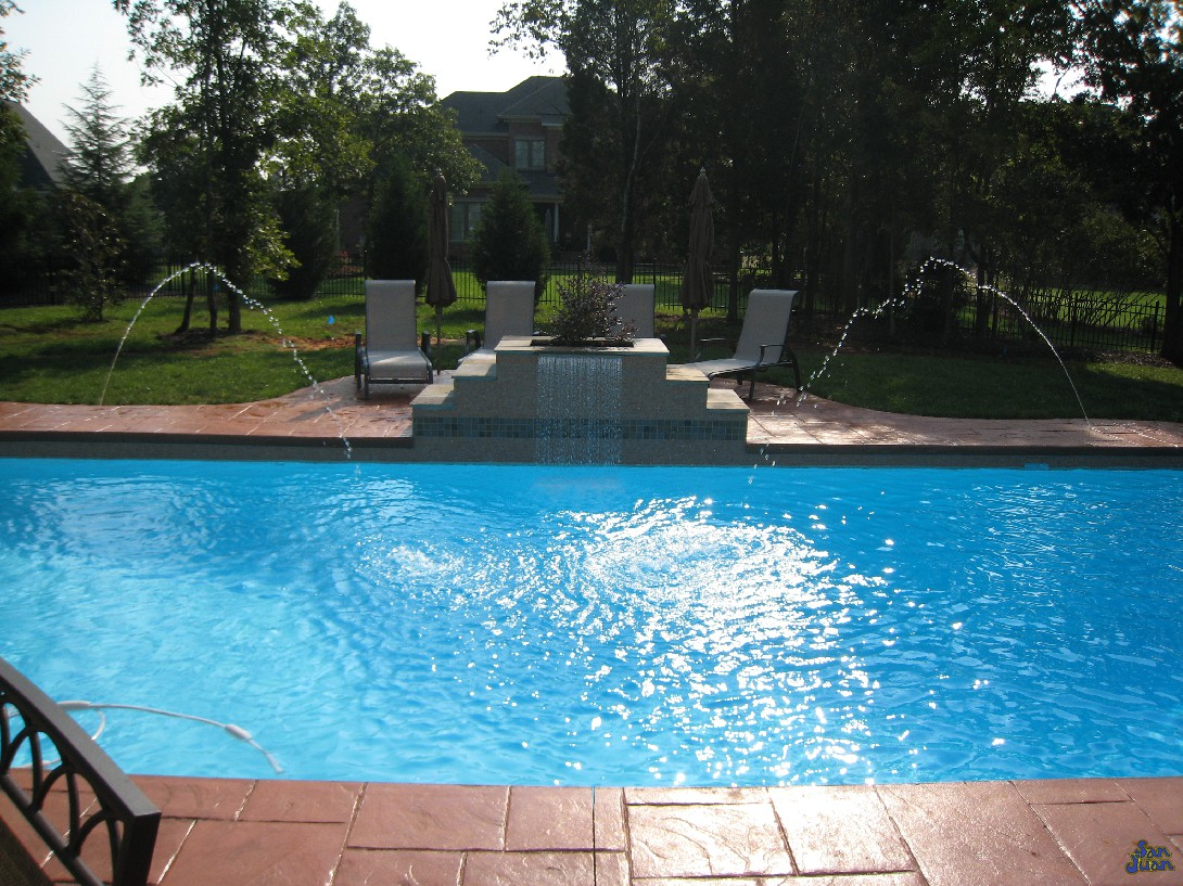 pacific fiberglass pool with raised waterfall and deck jets
