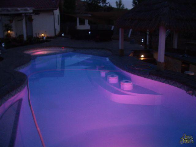 pleasure island fiberglass pool shape at night with purple led lighting