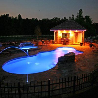 pleasure island fiberglass pool shape with led laminar technology at night