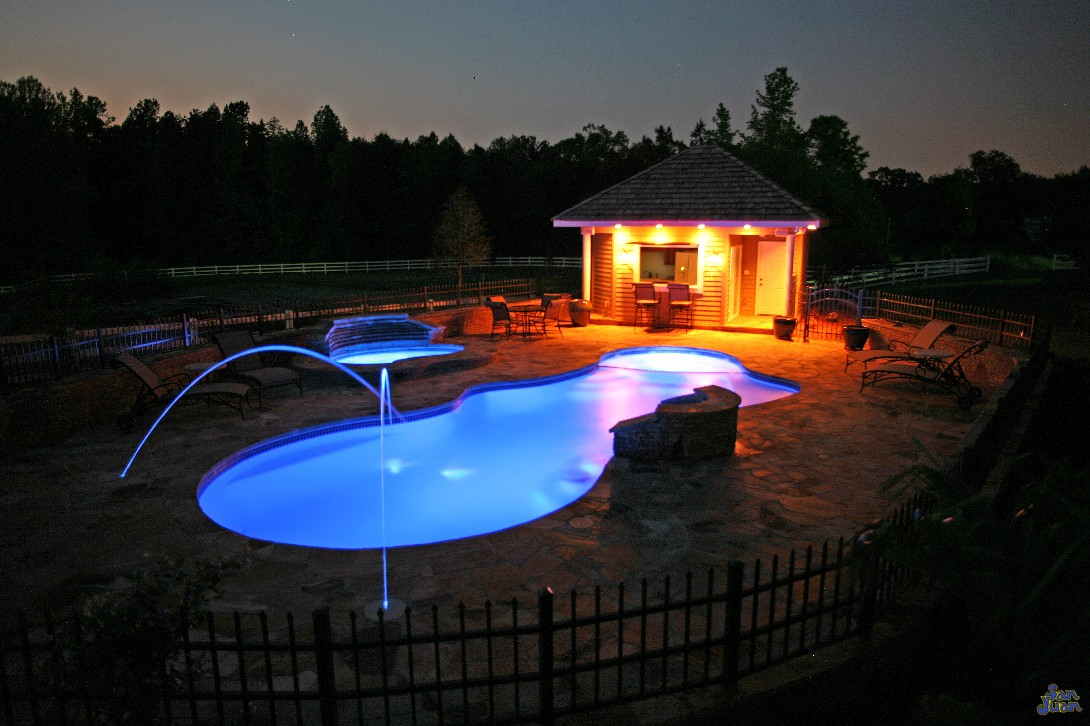 pleasure island fiberglass pool shape with led laminar technology at night