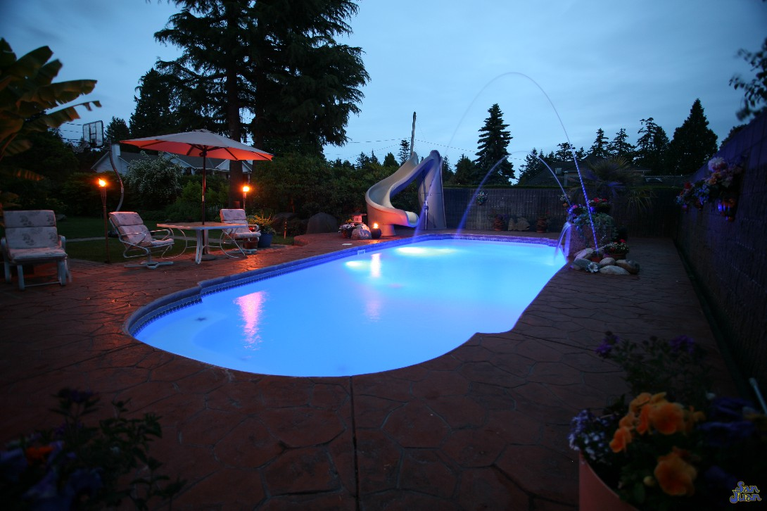 savannah deep pool shape at night with led lighting laminar jets slide and stamped stained concrete