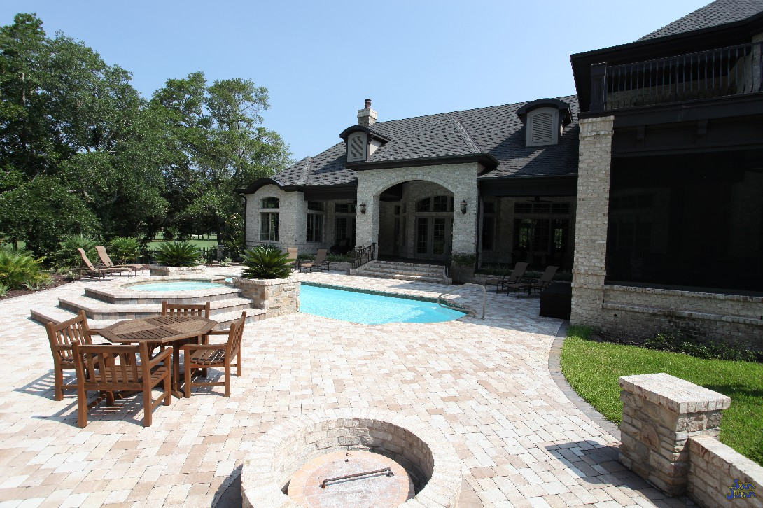 We'll give you one last sneak peak of what could be. This backyard includes gorgeous brick pavers, a fire pit next to a family dining area, raised spa and gorgeous landscaping. With a home like this - you've got a new meaning for Stay-cation!