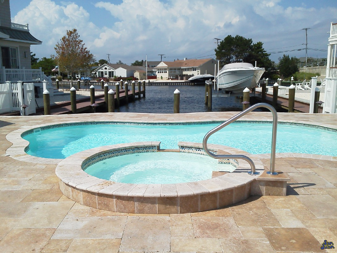 The Rio Fiberglass swimming pool is a compact swimming pool in a free form design. This image shows a Rio fiberglass pool installed with a connected round spa and travertine decking. Our swimming pools are compatible with all of our spa models and can be purchased as add-on's for any backyard design.