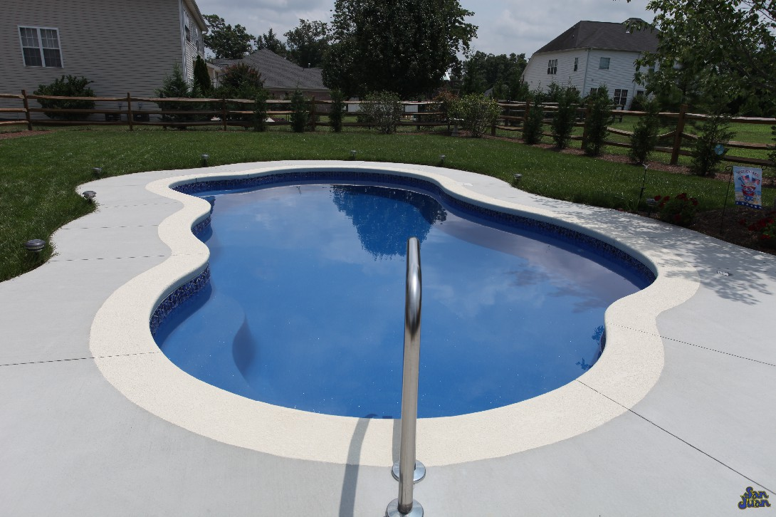 We love this gorgeous image of a Rio fiberglass shell with a Blue Lagoon gel coat. This image shows all of the modest curves from its free form design. This pool is built with a cantilever deck & stained concrete finish. As you can see here, adding a little more investment in a well poured deck goes a long way to boost the beauty of this swimming pool!
