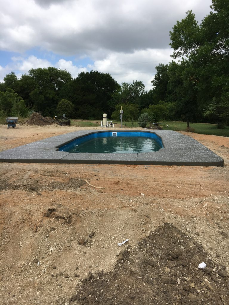 This is an image of our poured concrete deck - just resting and allowing it time to dry. We use some pretty amazing crews that have the capability of creating stamped, stained or textured concrete. This swimming pool is set with rock salt that dissolves to provide a natural texture to the concrete. More to come on this next week...