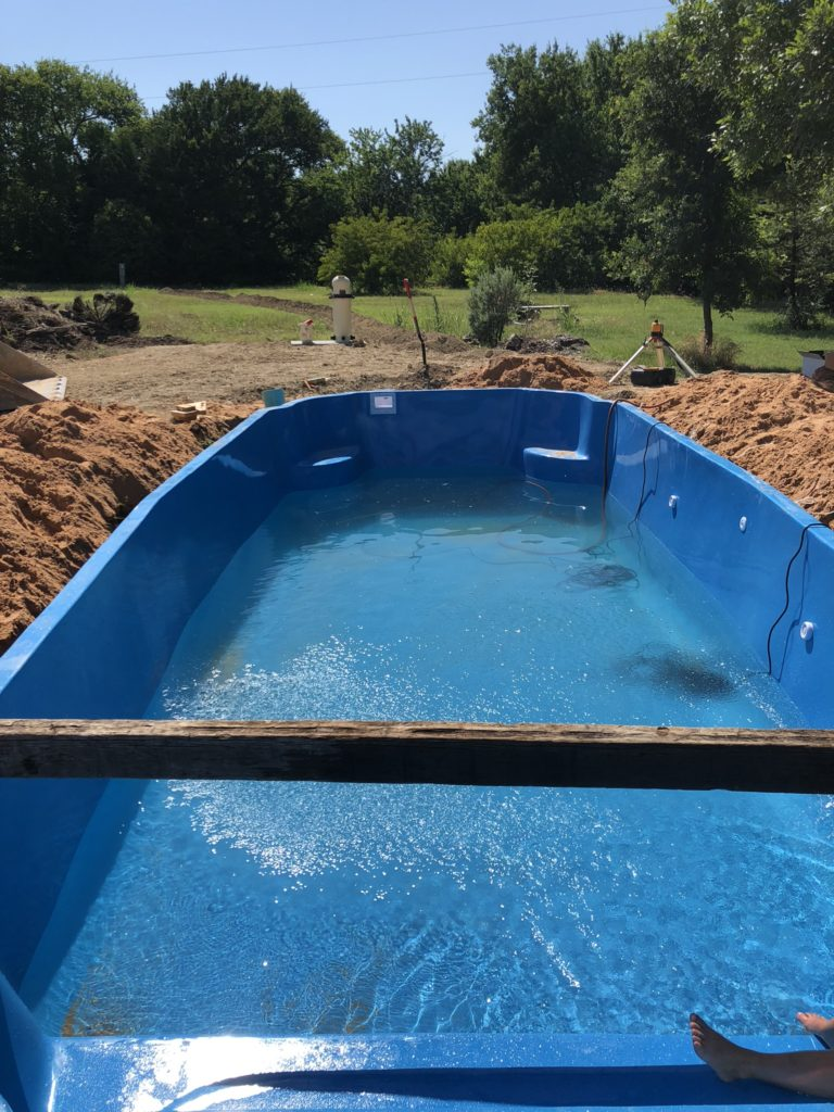 After we set our pool in our pre-dug hole, we slowly fill the pool shell with water. We must be careful during this stage to ensure that we do not knock the shell out of level. We take great care and re-shoot our elevations as the pool fills up and back fill to match the level of our water.