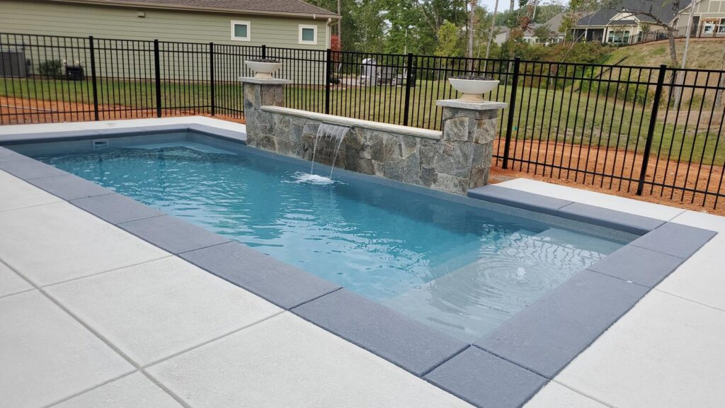 """The Biloxi is a rectangular swimming pool with a modern design. Outfitted with a narrow tanning ledge that runs the width of the pool, this design is great for leisurely activities. Additionally, the flat bottom design makes this extremely comfortable with a maximum depth of only 4' 2.5""""."""